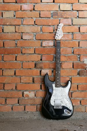 electric guitar leaning against brick wall Stock Photo