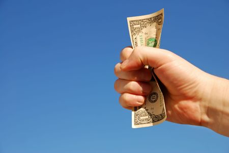 hand firmly holding one US dollar banknote against clear skies