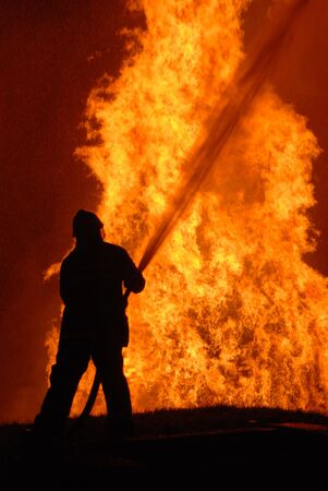 lone fireman battling against raging fire, NOTE: shallow focus on material burning in fire, top left corner particles from water spray, not camera noise Stock Photo - 7245237