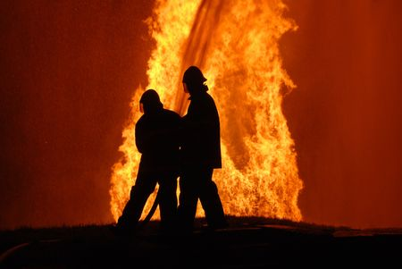 two firemen battling against raging fire, NOTE: top left corner particles are from fire and water spray, not camera noise Stock Photo - 7245236