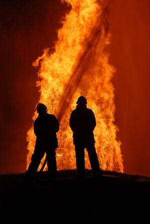 two firemen battling against raging fire, NOTE: top left corner particles are from fire and water spray, not camera noise Stock Photo - 7245235