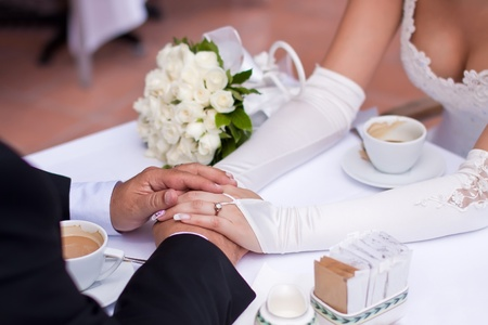 brides and grooms hands holding each other on a table Stock Photo