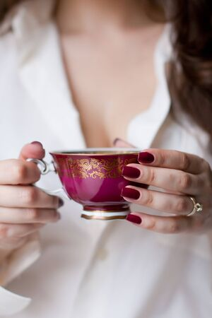 hands holding the cup of coffe