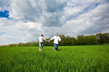 Happy young couple running in a green field