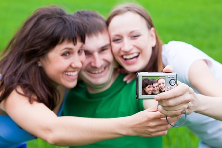Smiley People making a picture of themself on a grass photo