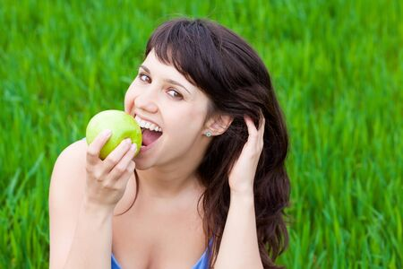 Girl eating a green apple on a grass