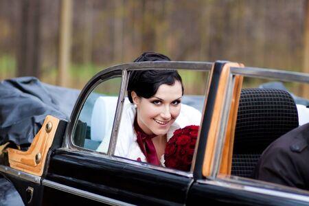 Beautiful bride in black retro car Stock Photo - 9689043