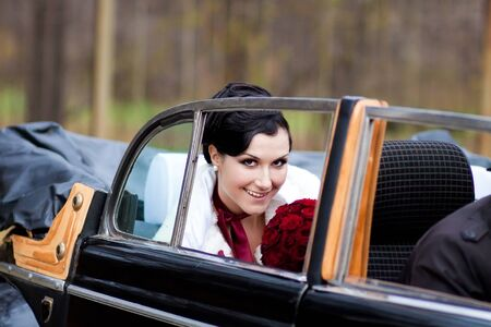 Beautiful bride in black retro car Stock Photo - 9689043