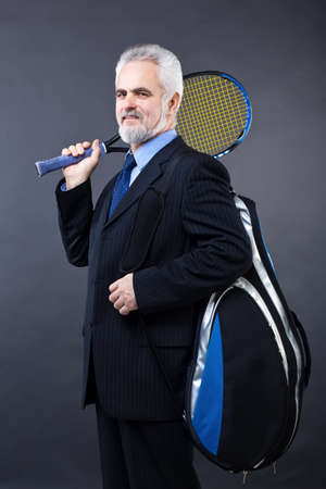 Studio shot of a smiling handsome business man who is going to play tennis