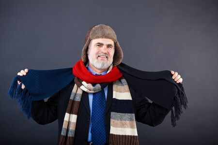 Studio shot of a smiling business man trying on an earfloped fur hat and different scarfs