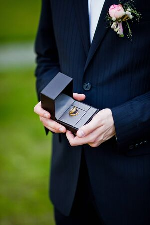 Groom holding his and bride s wedding rings in the black box Stock Photo