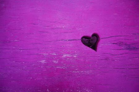 Close-up photogpraphy of the heart shape cut in the violet wooden background Stock Photo