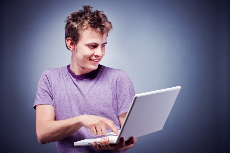 Studio shot of a young man using laptop photo