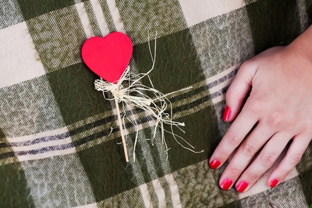 "WomanРІР'в""ўs hand and red heart-shaped candy on the checked plaid Stock Photo"