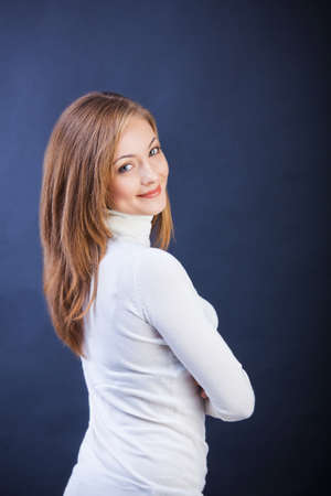 Studio shot of young caucasian smiling woman standing sidewise with crossed arms
