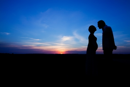 silhouette of a man and a pregnant woman on a sky