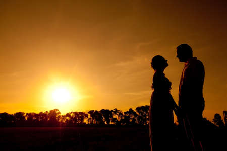Lover couple standing in sunset background silhouette Stock Photo