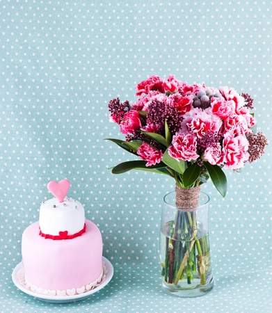 bouquet of flowers and cake with red hearts Stock Photo