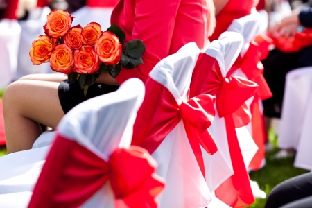 White wedding chairs decorated with red bows 스톡 콘텐츠