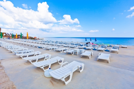 white lounge chairs on sea background