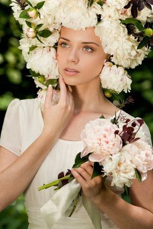 beautiful girl with flowes on the head in the forest
