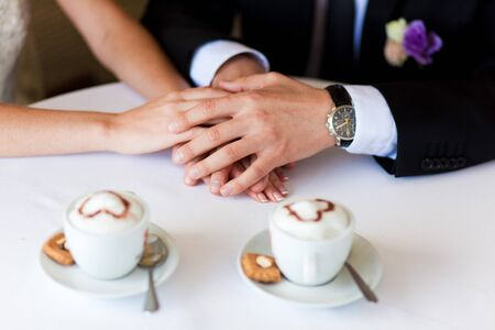 lovers holding hands on the table in cafe photo