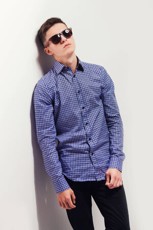 handsome fashion man wearing sunglasses thinking  photo