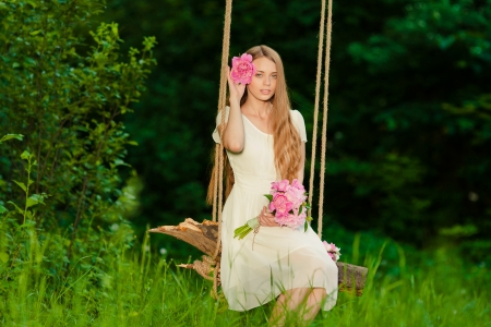 beautiful girl with bouquet of flowers in outdoor photo