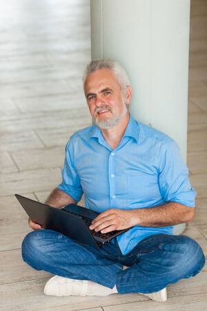 old man with notebook sitting on the floor Stock Photo