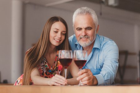 Senior man and his girlfriend drink wine on the kitchen