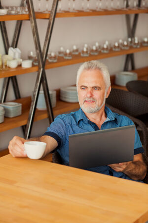 senior man with notebook sitting at the kitchen and drink coffee Stock Photo