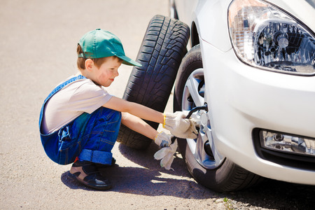 little boy repairing a car on the road