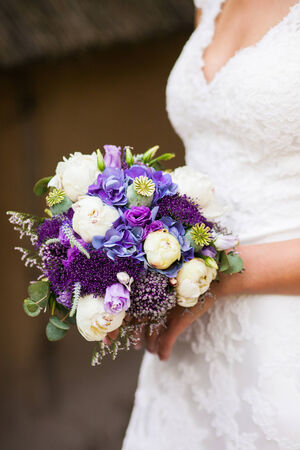 Beautiful bride in a white dress with a bouquet of flowers in hend