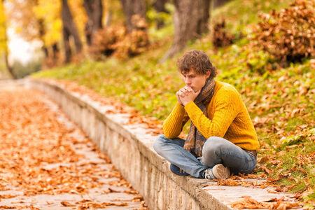sad curly man siting outdoor on autumn and thinking Standard-Bild