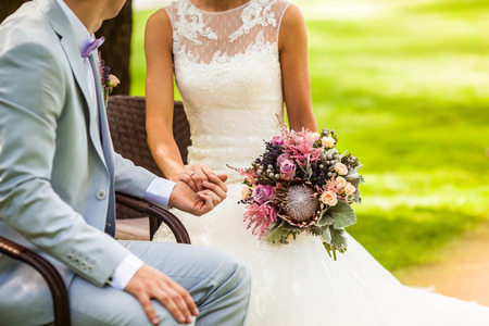 Wedding couple holding hands with wedding bouquet