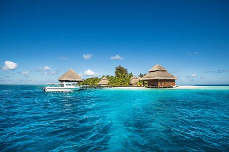 Beach Villas on small tropical island with cutter