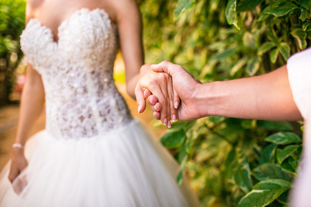 groom holding a brides hand outdoor Stock Photo