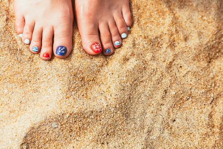 pedicura: Pies de la mujer con las uñas rojas en la arena de la playa natural de