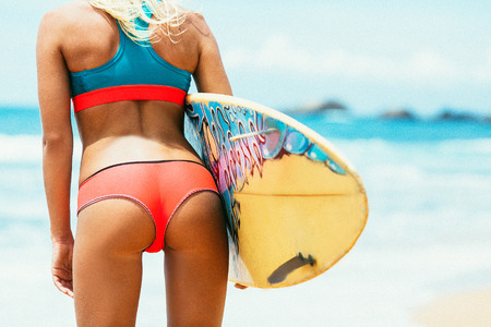 Rear view of beautiful sexy young woman surfer girl in bikini with color surfboard on a beach Stock Photo