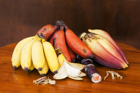 bananas with banana flower and sugar reed stick on wooden background Stock Photo