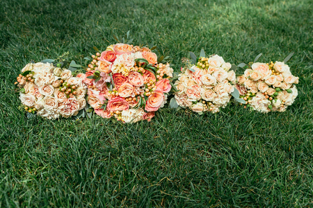 bridesmaids: Wedding bouquets of bride and bridesmaids on grass Stock Photo