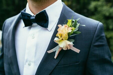 lapels: wedding boutonniere on suit of groom with bow-tie