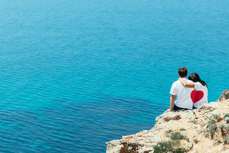 Man and woman siting on cliff together in love with heart shape on theirs t-shorts Stock Photo