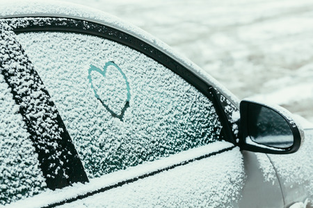 Heart drawn on a car windshield covered with fresh Christmas snow