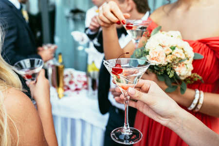 martini glasses: girls Drinking martini cocktails with red cherry on the wedding