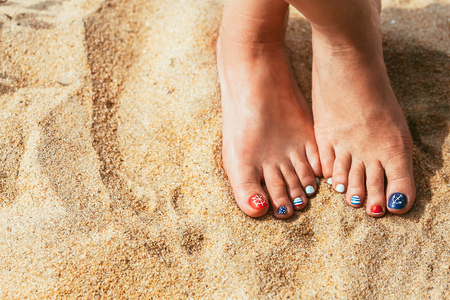 toenails: Woman feet with red toenails on natural beach sand