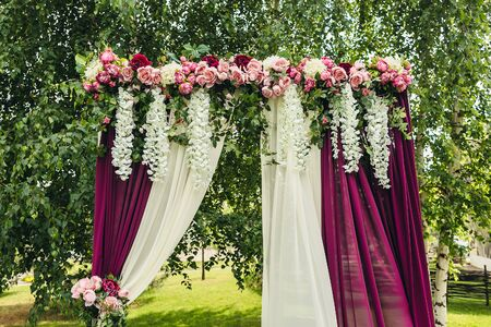 wedding arch with flowers situated in forest. Wedding ceremony in marsala style Stock Photo