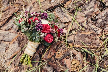 Rustic wedding bouquet with red and lilac roses on bark background Stock Photo