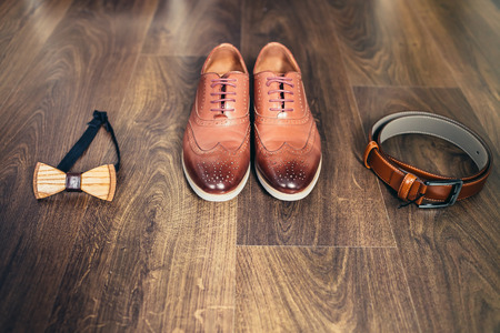 Wedding set of mens stylish shoes, wooden bow-tie and belt on a brown wooden background Stock Photo