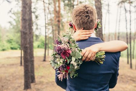 bride huging groom with lilac roses wedding bouquet on wedding ceremony in forest